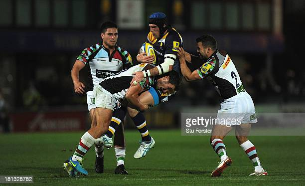 Worcester player Jon Clarke runs into Harlequins players George Lowe and Karl Dickson during the Aviva Premiership match between Worcester Warriors...