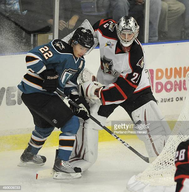 Worcester's Tim Kennedy fights with Pirates goalie Mark Visentin behind the goal as the Portland Pirates host the Worcester Sharks at the...
