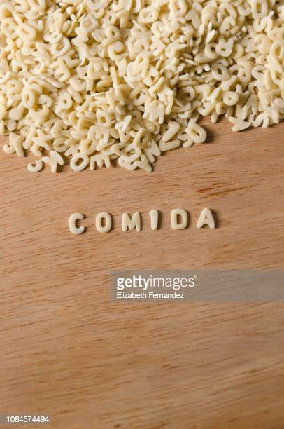 """Word """"Comida"""" made of alphabet pasta on wooden table background"""