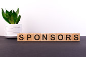 SPONSORS word concept written on wooden blocks, cubes on a dark table with a flower and a light background