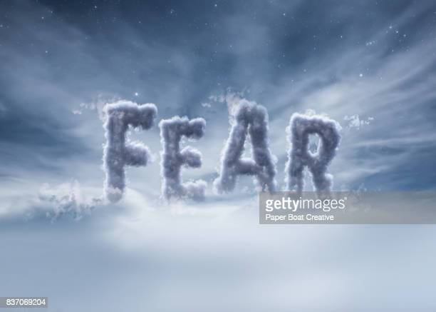 word fear show with a heavy cloud typeface up against dark clouds in the sky - typographies stock photos and pictures