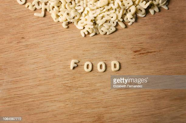 """Word """"Food"""" made of alphabet pasta on wooden table background"""