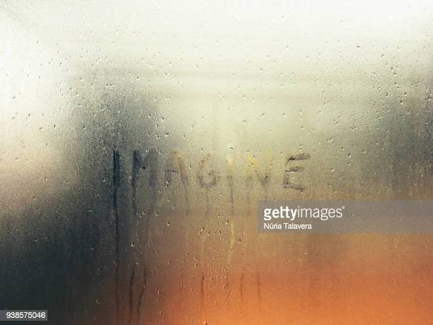 word 'imagine' written on a glass surface fogged by the rain - imaginación fotografías e imágenes de stock