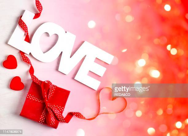 Word Love and red gift box at white background copy space