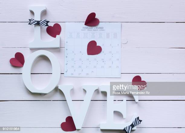 Word love written with wooden letters, calendar sheet, paper heart shapes and bow tie on wooden background Top view and copy space