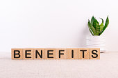 BENEFITS word made with building blocks on a light background