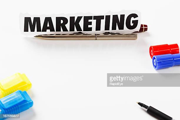 Word Marketing and pens form a border on white background