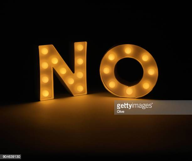 Word NO written with illuminated letters in dark