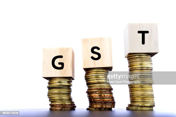 GST Word on Wood Block on Top of Coins Stack