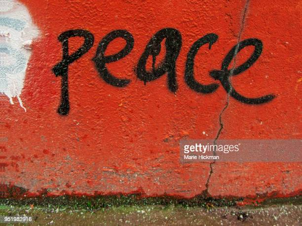 Word PEACE hand written on an orange wall.
