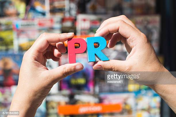 Word PR in front of kiosk for selling newspapers and magazines, hands holding wooden letters