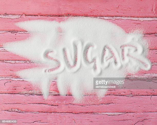 Word sugar written in sugar on pink wooden table