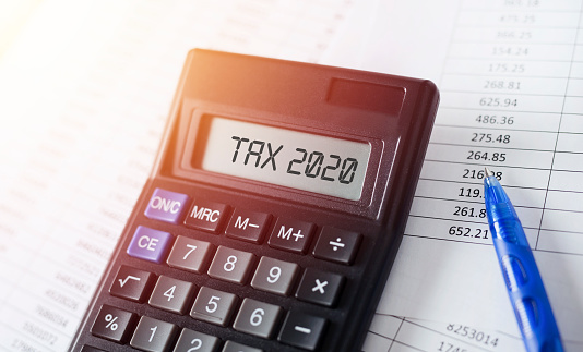 Word Tax 2020 on calculator. Business and tax concept. 1176289284