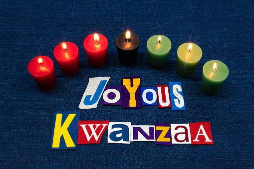 JOYOUS KWANZAA word text collage typography, seven candles and multi colored fabric on blue denim, African American holiday 1166662182