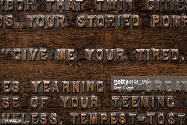 Words from 'The New Colossus' poem by Emma Lazarus are engraved on a replica bronze plaque inside the Statue of Liberty Museum on Liberty Island...