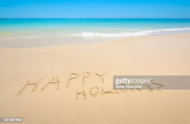 """words """"happy holidays"""" written in the sand of a tropical beach. - happy holidays stock photos and pictures"""