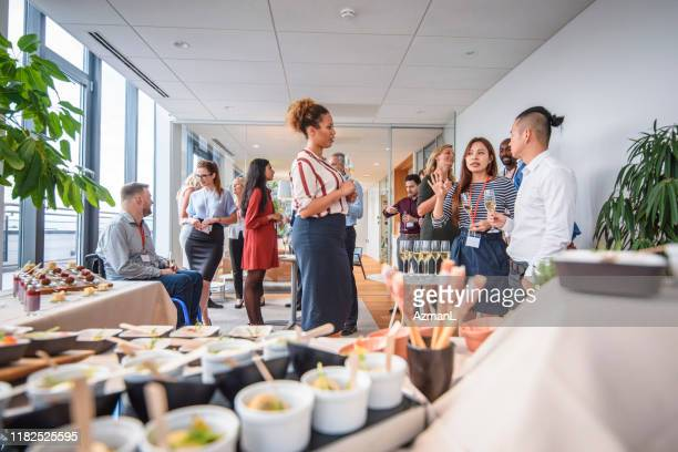 work associates enjoying food and sparkling wine at party - entertainment event stock pictures, royalty-free photos & images