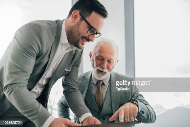 work associates revising paperwork - two generation family stock pictures, royalty-free photos & images