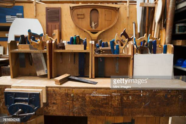 Work bench in a boat-builders workshop, selection of hand tools for wood working.
