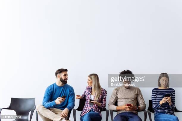 werken van kandidaten die met behulp van mobiele telefoon tijdens het wachten voor sollicitatiegesprek - kandidaat stockfoto's en -beelden
