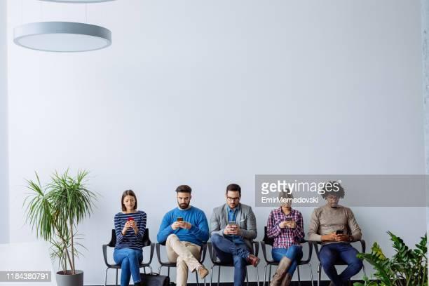 candidats au travail utilisant des téléphones mobiles en attendant l'entrevue d'emploi - candidat photos et images de collection