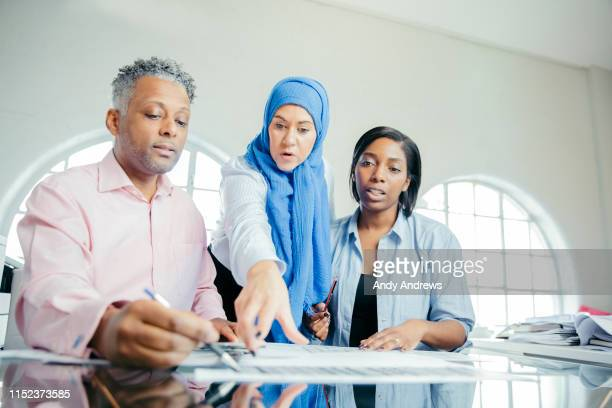 work colleagues discussing a project - afro caribbean ethnicity stock pictures, royalty-free photos & images