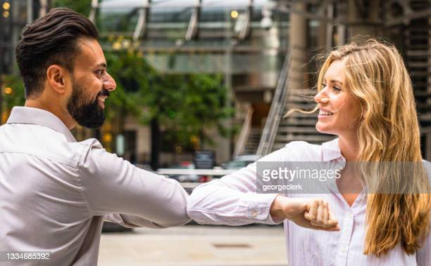 work colleagues elbow bumping as they meet - employee stock pictures, royalty-free photos & images