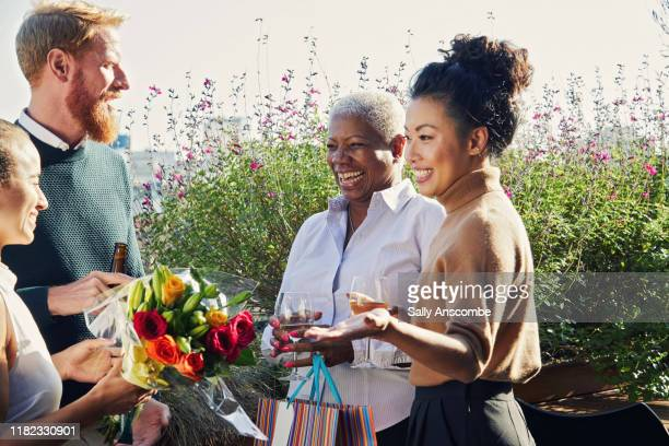 work colleagues giving a gift and flowers - sally anscombe stock pictures, royalty-free photos & images