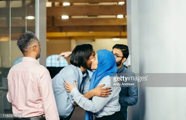 work colleagues hugging in office - care stock pictures, royalty-free photos & images