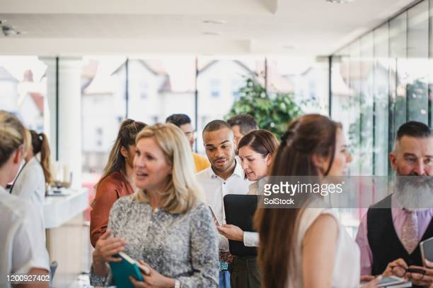 work colleagues meeting and talking in corporate building - event stock pictures, royalty-free photos & images