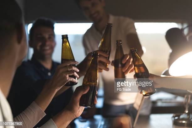 work colleagues toasting with beers in the office, after working late - five people stock pictures, royalty-free photos & images