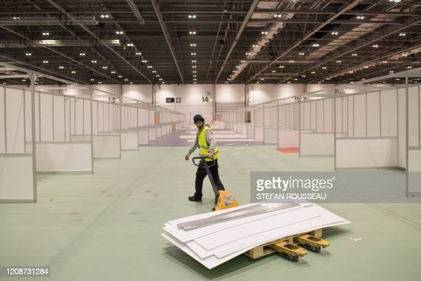 Work continues by members of the military and private contractors inside the ExCel centre in London on March 31 which has been transformed into a...