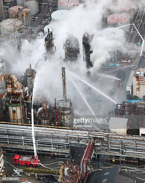 Work continues to extinguish a fire at a TonenGeneral Sekiyu KK oil refinery in Arida Wakayama Prefecture western Japan in this photo taken from a...