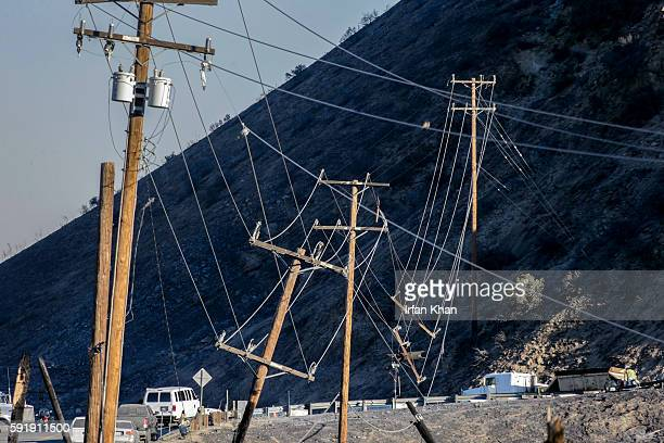 Work crew prepare to repair power lines downed due to the Blue Cut fire on Highway 138 at the junction of 15 Freeway