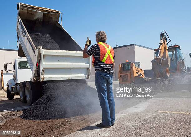 Work crew repairing pot holes in a parking lot