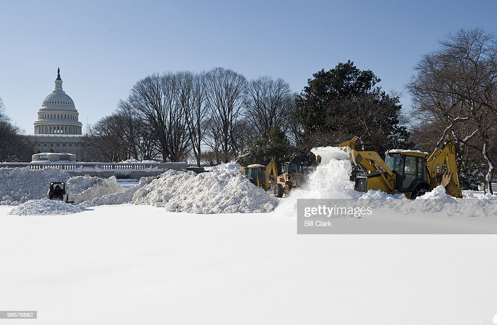 Work crews push snow into the reflecting pool on north side of the Capitol on Monday, Feb. 8, 2010, following the weekend's historic snowstorm. Dump trucks loadedc with snow from around the US Capitol lined up to dump their loads at the site.