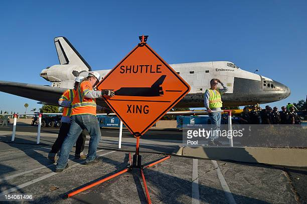 Work crews set up a sign as the Space Shuttle Endeavour arrives at the Forum enroute to the California Science Center on October 13 2012 in Inglewood...