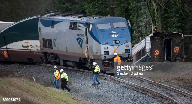 Work crews survey the scene of an Amtrak train derailment on December 18 2017 in DuPont Washington At least six people were killed when a passenger...