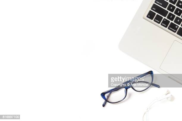 Work desk top view simple white background image with laptop, eye glass and earphone