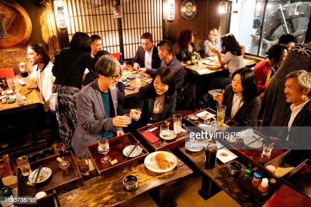 trabajar amigos que se tuestan en japonés izakaya - atestado fotografías e imágenes de stock