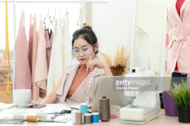 work from home. asian young woman fashion designer  working on her design in the showroom.  lifestyle people stylish tailor taking measurements on mannequin in studio.  business small concept - ribbon sewing item stock pictures, royalty-free photos & images