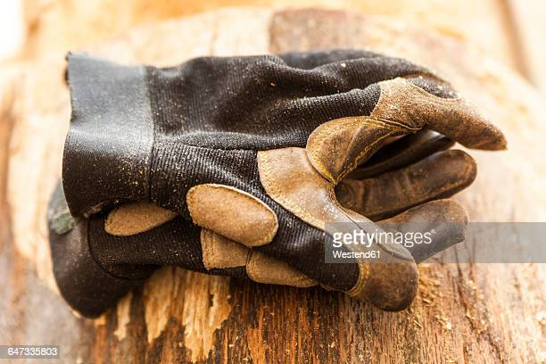 work gloves on wood block in wood carver's workshop - work glove stock photos and pictures