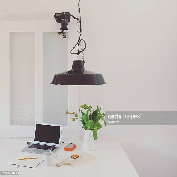 Work hard anywhere. Working from home. Laptop on a desk in a living room or modern kitchen. Home office. Camera mounted on door.