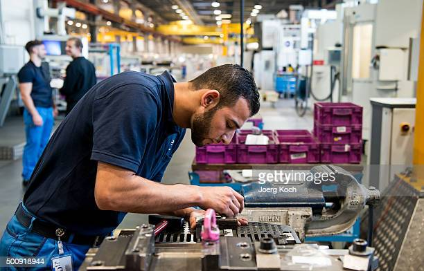 Work Here participant a refugee from Syria who came to Germany one year ago trains and works at the BMW factory on December 3 2015 in Munich Germany...