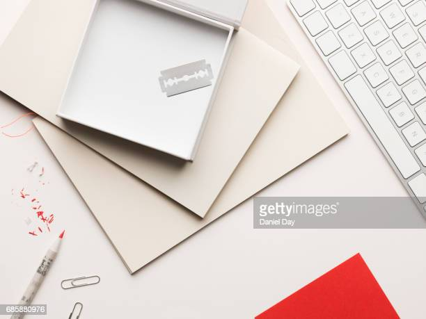 work or home desk with a pile of notebooks and an open box containing a razor blade on top, broken red pencils and red shavings representing blood - self harm stock photos and pictures