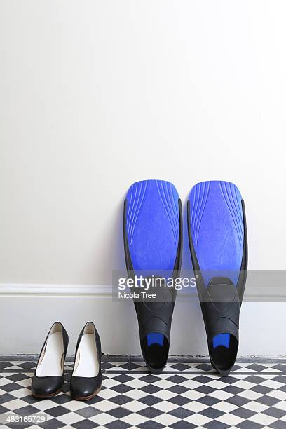 Work shoes next to diving flippers in hallway