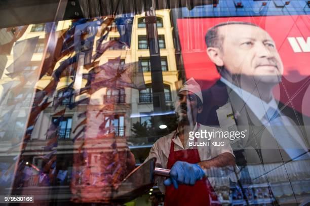 TOPSHOT A work slices meat as he stands in the window of a Turkish restaurant under a portrait of Turkish President Recep Tayyip Erdogan on Taksim...