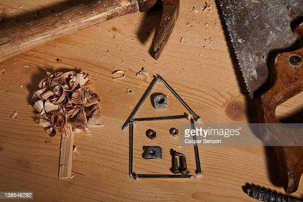 work tools surrounding a house made of nails and tree made of wood shavings - nuts models stock pictures, royalty-free photos & images