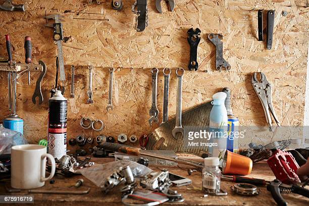A workbench and tool board in a cycle repair shop. Coffee mug, hand tools, nuts and bolts and spanners.