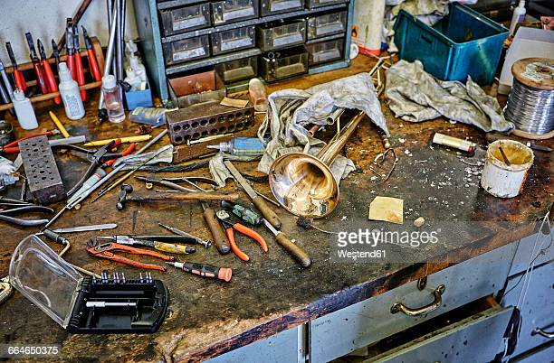 Workbench of an instrument maker with tools and trumpet